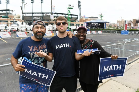 Andrew Yang supporters, from left, Andrew Mendieta, 39, of West Palm Beach, Florida; Robb Maddox, 24, of Athens, Georgia and Alyssa Mason, 21, of Wilmington, Delaware pause for a photo while checking out the scene on Woodward Avenue near the Fox Theatre in Detroit Monday afternoon.