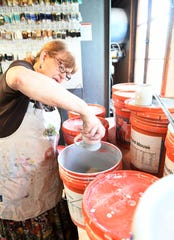 Rosi Triano of Grosse Pointe Farms dips a stoneware mug into a bucket of glaze to create a stripe effect in the studio at Pewabic Pottery in Detroit.