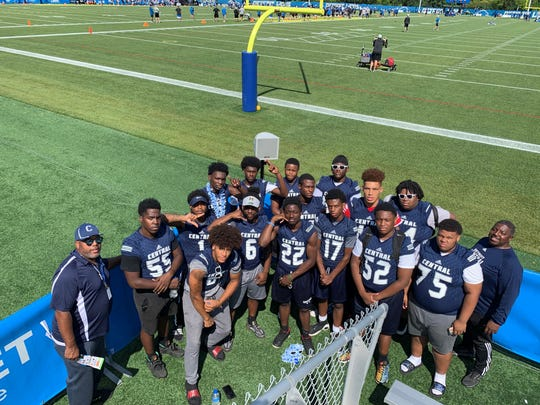 Members of the Detroit Central High varsity football team, along with coaches Jimmy Macon and Keith King, pose for a picture Tuesday at Lions training camp.