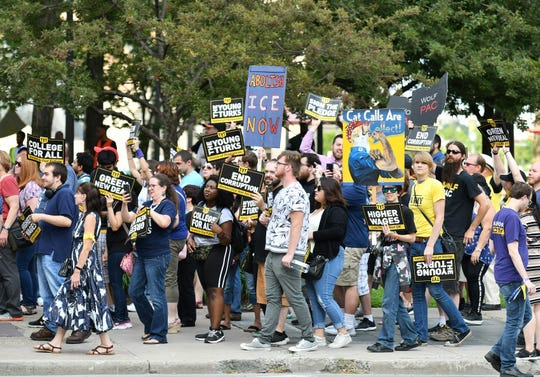 The Young Turks, an organization of progressive Democrats, march up Woodward Avenue with signs and chanting Tuesday before the first Democratic presidential debate in Detroit.