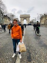 Logan Zieber shops on the Avenue des Champs-Élysées in Paris with the Arc de Triomphe in the background.
