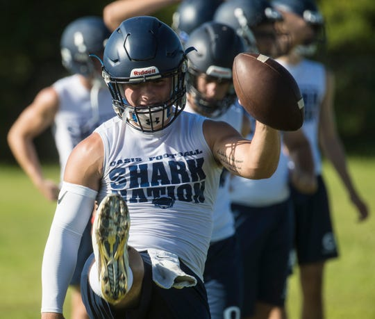 Daniel Rennie, the quarterback at Oasis High School in Cape Coral practices with teammates on Tuesday July, 30, 2019. He along with his brother, Tanner lead the team.