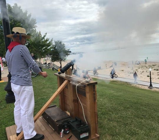 Smoke billows from a swivel gun fired by maritime historian and retired U.S. Coast Guard Capt. Bob Desh as a greeting salute over Crescent Beach to the tall ships mustered in Lake Michigan off the Algoma shore.