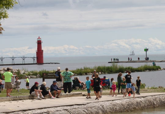A tall ship on the horizon sails past Algoma Pierhead Lighthouse as people gather on Crescent Beach to view the five of the ships in Lake Michigan at full sail.
