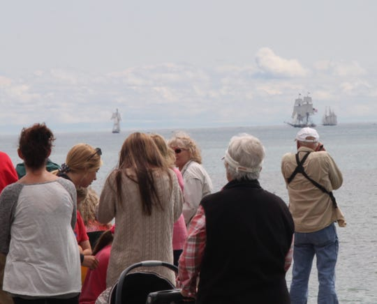 A crowd of people gather near the end of the pier off Crescent Beach in Algoma to view and take photos of of the tall ships in Lake Michigan at full sail as begin their way south down Lake Michigan for the Great Lakes Challenge race.