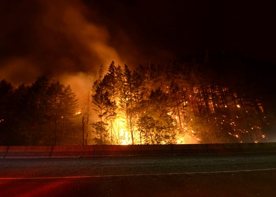 In this Saturday, July 27, 2019 photo, flames rage next to Interstate 5 south of Canyonville, Ore., during the Milepost 97 Fire. Interstate 5 drivers should expect delays Tuesday, July 30, 2019, in both directions as fire crews remove hazardous trees south of Canyonville in southwestern Oregon. The Oregon Department of Transportation says traffic will be slowed in both directions between mileposts 88 and 101 from 7 a.m. to 10 a.m. Oregon's Milepost 97 fire is believed to have started Wednesday because of an illegal campfire. (Jon Mitchell/The News-Review via AP)