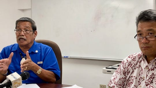 Sen. Joe San Agustin, left, goes over the details of his fiscal 2020 budget bill, while Office of Finance and Budget Director Stephen Guerrero, right, looks on, at a news briefing on July 30, 2019 in Tamuning.