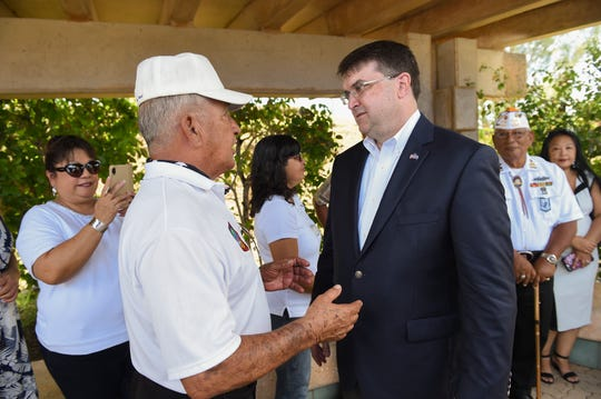"""Robert Wilkie, U.S. Secretary of Veterans Affairs, right, meets with Johnny """"Atulai"""" Taitano, Military Order of the Purple Heart commander and Guam Veterans Commission vice-chairman, at the Asan Bay Overlook in Asan, July 30, 2019."""