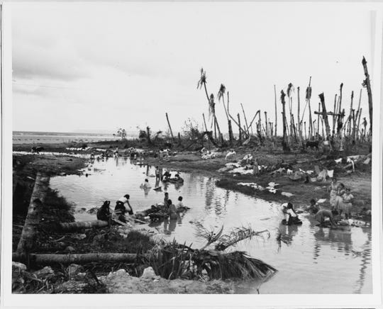 Woman washing cloths in a creek near Agana on Aug. 12, 1944. The order was given on Aug. 3 to return civilians to safe areas on the island.
