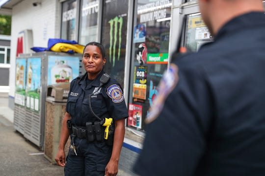From left, downtown district patrol officers Yolanda Burns and AJ Francis talk after completing a call related to panhandling Indianapolis, Monday, July 29, 2019.