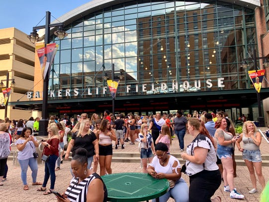 Fans mill around outside Bankers Life Fieldhouse after the announcement that Tuesday's Cardi B show had been postponed to Sept. 11.