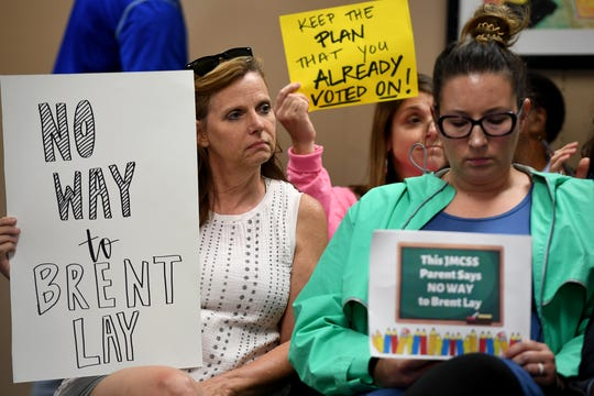 Parents of Jackson-Madison School students hold up signs in protest of Brent Lay during a long-range planning committee meeting at the Jackson-Madison County School's central office, Tuesday, July 30.