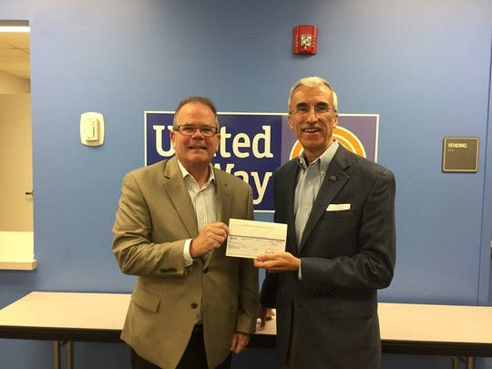 Alan Hill, regional director at AT&T, presents a check from AT&T to United Way of Greater Knoxville president and chief executive officer Ben Landers in 2018.