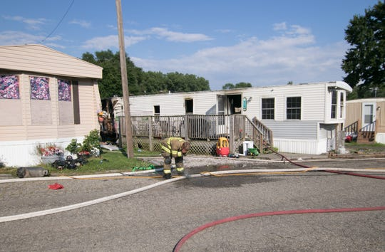 A Northfield Township firefighter washes his face using spray from a fire hose as other firefighters tend to a fire in a mobile home on Floreen Lane Tuesday, July 30, 2019 in Green Oak Township.