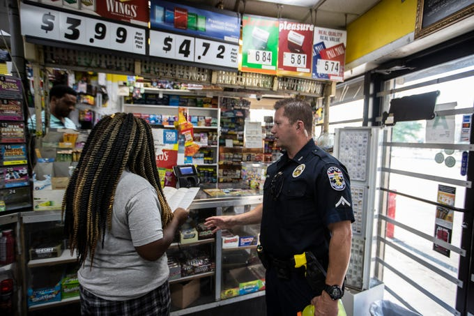 Louisville Metro police officer Tony Sacra hands crime prevention literature to a woman in a food mart on west. Broadway, July 29, 2019.