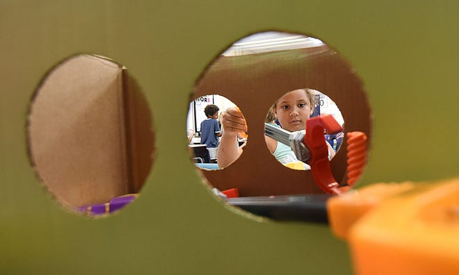 Amora Howard, 7 years old, uses a grabber to simulate how astronauts work in space during the LEXplore Science Camp at Lexington Eastern Elementary.