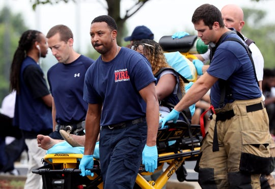 A Walmart employee is attended to by EMS officials following a shooting Tuesday morning, July 30, 2019, that killed two and injured two others.