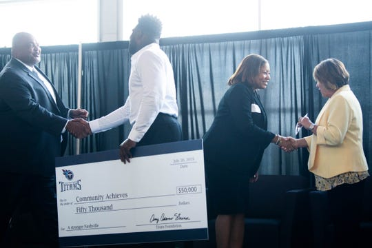 MNPS Interim Director Dr. Adrienne Battle shakes hands with Titans controlling owner Amy Adams Strunk as Dr. Tony Majors shakes Delanie Walker's hand before receiving a check for Community Achieves at Nissan Stadium Tuesday, July 30, 2019, in Nashville, Tenn.