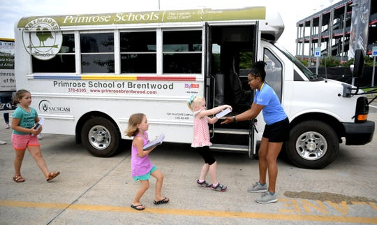 Local Primrose students help deliver collected notebooks to United Way's Dandrea Alexander at Nissan Stadium on Tuesday, July 30, 2019. Local Primrose schools donated to United Way's Stuff the Bus campaign to provide backpacks to students in need from more than 14 local schools.