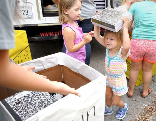 Lennon Clopton,2, helps load a school bus with collected notebooks at the Primrose School of Nashville Midtown on Tuesday, July 30, 2019. Local Primrose schools collected school supplies as part of United Way's Stuff the Bus campaign to provide backpacks to students in need.