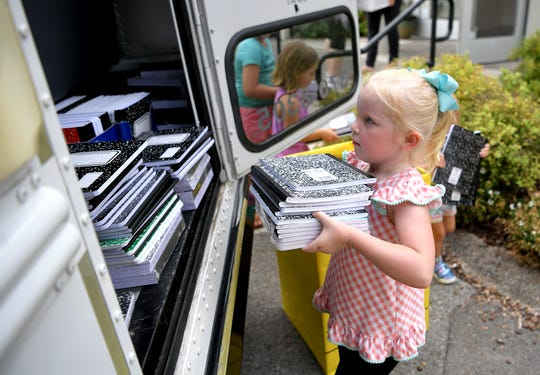 Lyla Shanaman,5, helps load a school bus with collected notebooks at the Primrose School of Nashville Midtown on Tuesday, July 30, 2019. Local Primrose schools collected school supplies as part of United Way's Stuff the Bus campaign to provide backpacks to students in need.