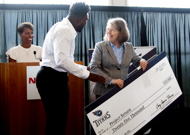 Project Return's Bettie Kirkland smiles with Delanie Walker and Tina Tuggle after receiving a check for Project Return at Nissan Stadium Tuesday, July 30, 2019, in Nashville, Tenn.