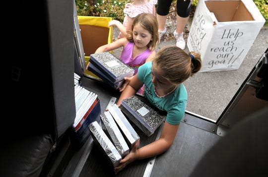 Bea James,4, and Rosy James,7, help load a school bus with collected notebooks at the Primrose School of Nashville Midtown on Tuesday, July 30, 2019. Local Primrose schools collected school supplies as part of United Way's Stuff the Bus campaign to provide backpacks to students in need.
