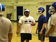 Titusville football coach Paul Columna leads practice Tuesday, July 30, 2019, in the school gym after lightning forced the team inside.