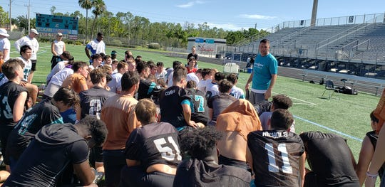 Gulf Coast High School football coach Tom Scalise (standing right) talks to his team following practice on Tuesday, July 30, 2019. Scalise is entering his second season as the Sharks' head coach.