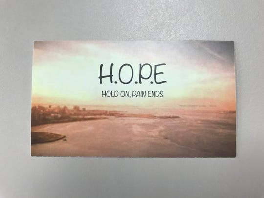 "A card given out by Mental Health America of Licking County depicts the phrase ""H.O.P.E. Hold on, pain ends"" on one side. The other side lists suicide risk factors and resources."