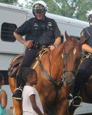 Corporal David Carra laughs as Asiya Hatcher, 6, talks horse sense with Baron, the police horse in Main Memorial Park during Clifton's annual National Night Out on Aug. 2, 2016,.