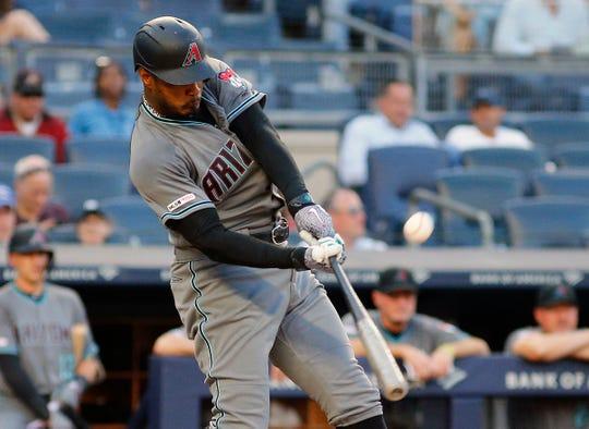 Jul 30, 2019; Bronx, NY, USA; Arizona Diamondbacks right fielder Adam Jones (10) hits an RBI sacrifice fly against the New York Yankees during the first inning at Yankee Stadium.