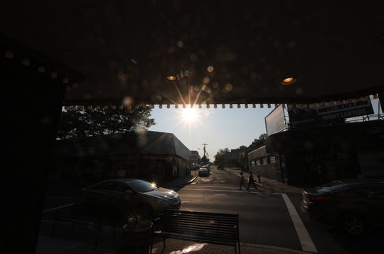 People cross the street in front of the Cinema 5, in Bergenfield, as the sun rises Tuesday morning.  Temperatures will rise to at least 90 degrees, to cap off the second heat wave this month.  July 30, 2019