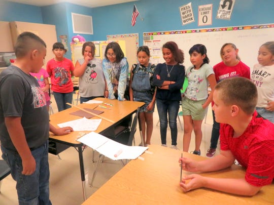 Bataan Elementary fifth-grade students observed one group's demonstration of how strong their bridge is by distributing rolls of pennies on the bridge. Fifth-grade teachers Gina Simms, Melissa Noriega, and Kim Perea all agreed that the students had a great time working on the bridge unit.