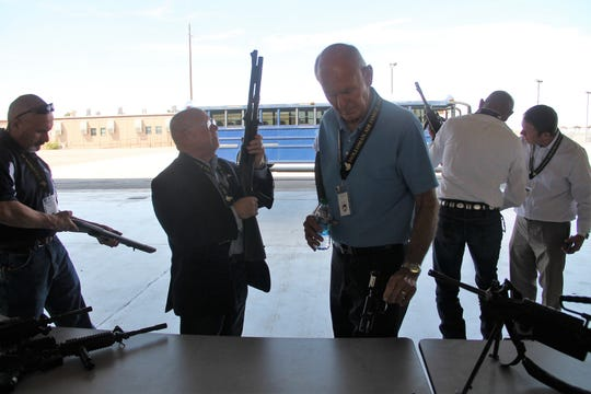 "Alamogordo Mayor Richard Boss  New Mexico State Senator William  ""Bill"" Burt look at weapons on the 49th Mission Support Group table at the Holloman Air Force Base Civic Leaders Open House July 29."