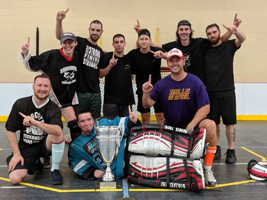The Michigan Ball Hockey A League Champion Balls of Steel are pictured with the Sarkisoff Cup. Pictured in front are Brandon McCullough, Cam Wolford and Mark Robert. In back are Anjanette Rieger Delgado, Tim Domzalski, Nick Martell, Ryan McCullough, Ed Hendricks and Josh Helig.
