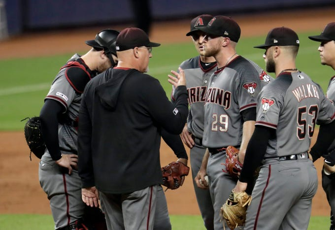 Arizona Diamondbacks pitching coach Mike Butcher, second from left, talks with starting pitcher Merrill Kelly (29) during the second inning of a baseball game against the Miami Marlins, Monday, July 29, 2019, in Miami. The Marlins scored six runs in the second inning. (AP Photo/Lynne Sladky)