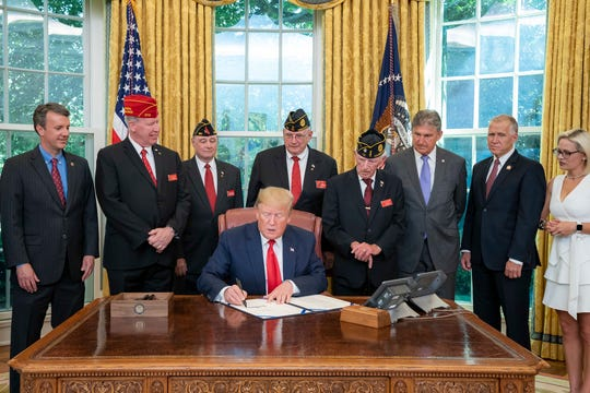 Pres. Donald Trump signs a bill sponsored by Sen. Kyrsten Sinema, D-Ariz., that will expand access to American Legion membership.