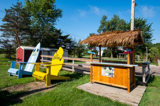Surfboard-style bars with thatched roofs are one of the more popular items made by Tiki Republic in Smiths Creek, although they also build giant ottoman chairs painted with different themes, among other items.