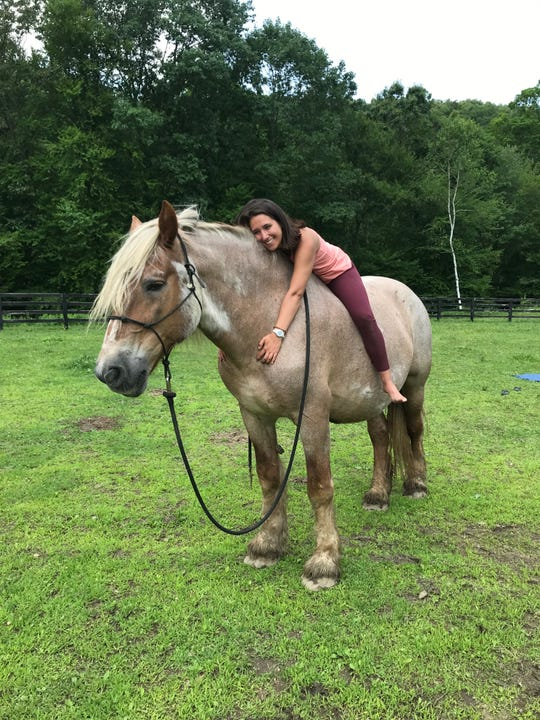Courtney Colella relaxes in a pose on Pom the horse at Lucky Orphans Horse Rescue in Dover Plains. Colella leads yoga classes there using horses.
