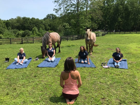 Courtney Colella leads a yoga class at Lucky Orphans Horse Rescue in Dover Plains.