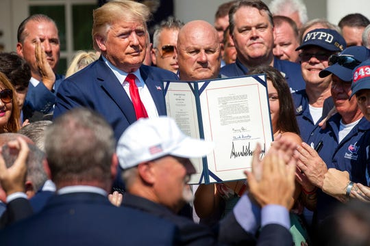 President Donald Trump is surrounded by first responders after signing H.R. 1327, an act ensuring that a victims' compensation fund related to the Sept. 11 attacks never runs out of money, in the Rose Garden of the White House, Monday, July 29, 2019, in Washington. (AP Photo/J. Scott Applewhite)