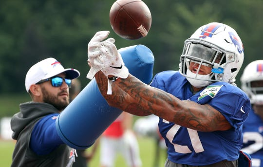 Safeties coach Bobby Babich wears a piece of equipment the Bills are trying that will get the defensive backs out of the habit of grabbing receivers.