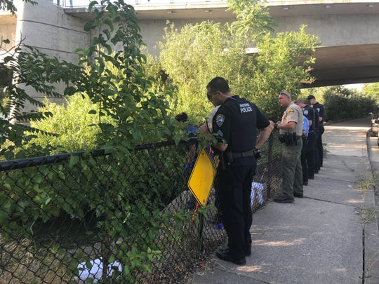 Law enforcement officers from the Redding Police Department and Shasta County Sheriff's Department on Tuesday, July 30, 2019 survey the area under the Cypress Avenue bridge at Park Marina Drive.
