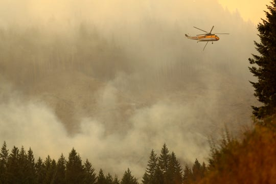 A helicopter flies through smoke lingering from the Milepost 97 Fire near Azalea in southern Oregon on July 29, 2019.