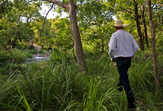 Brian Treadwell walks toward the waterfall near the ceremony site at the South Concho River Falls wedding venue Tuesday, July 30, 2019.
