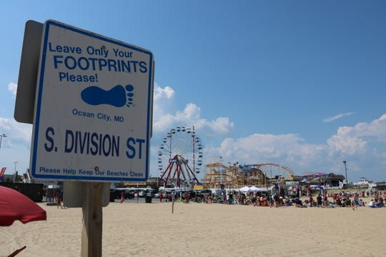 """An anti-littering sign posted on the beach at Ocean City, Maryland, Monday, July 29, 2019, asks visitors to """"leave only your footprints."""" The town of Ocean City initiated a program this month to incentivize businesses to hand out fewer disposable plastic items. (Julia Rentsch / Salisbury Daily Times)"""