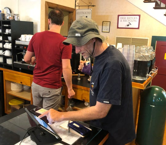 Joseph White rings up a customer's order at Cranberry's in Staunton on Monday. White wasn't scheduled to return to his store in July, but he broke his wrist on the Appalachian Trail and had to end his hike about a month early.