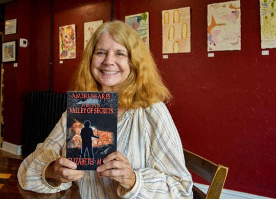 "Local author Elizabeth Massie poses with one of her ""Ameri-Scares"" books on Tuesday, July 30, 2019. Massie is in the process of writing 50 books for the series, one for each state, based on folk tales, legends and historical events. She is currently writing the 10th book in the series."