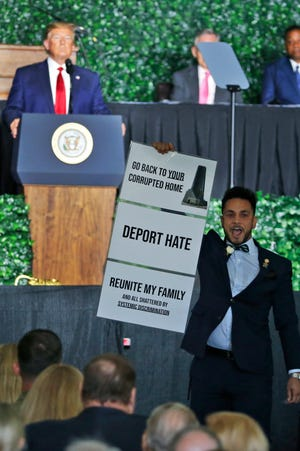 President Donald Trump waits as a protester holds a sign and yells while addressing a commemorative meeting of the Virginia General Assembly at Jamestown Settlement on the 400th anniversary of the meeting of the original House of Burgess in Jamestown, Va., Tuesday, July 30, 2019. (AP Photo/Steve Helber)